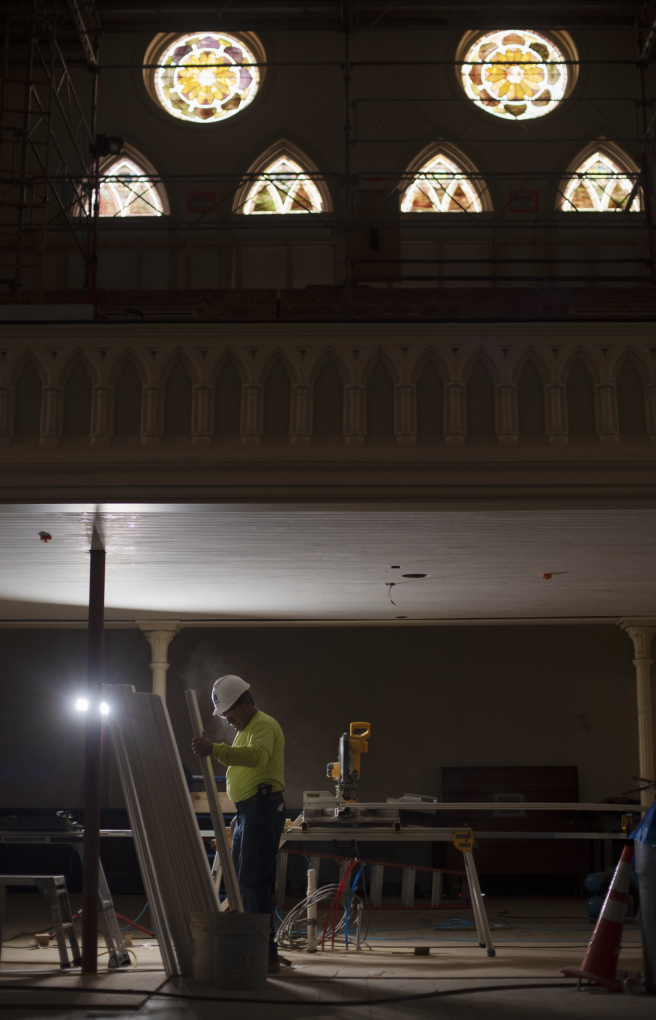 A construction worker is lit by worklight as sun streams through stained glass in the balcony of the great hall during construction at UPH Monday, Novermber 11, 2019. Photo credit: Kate Penn - Proctors