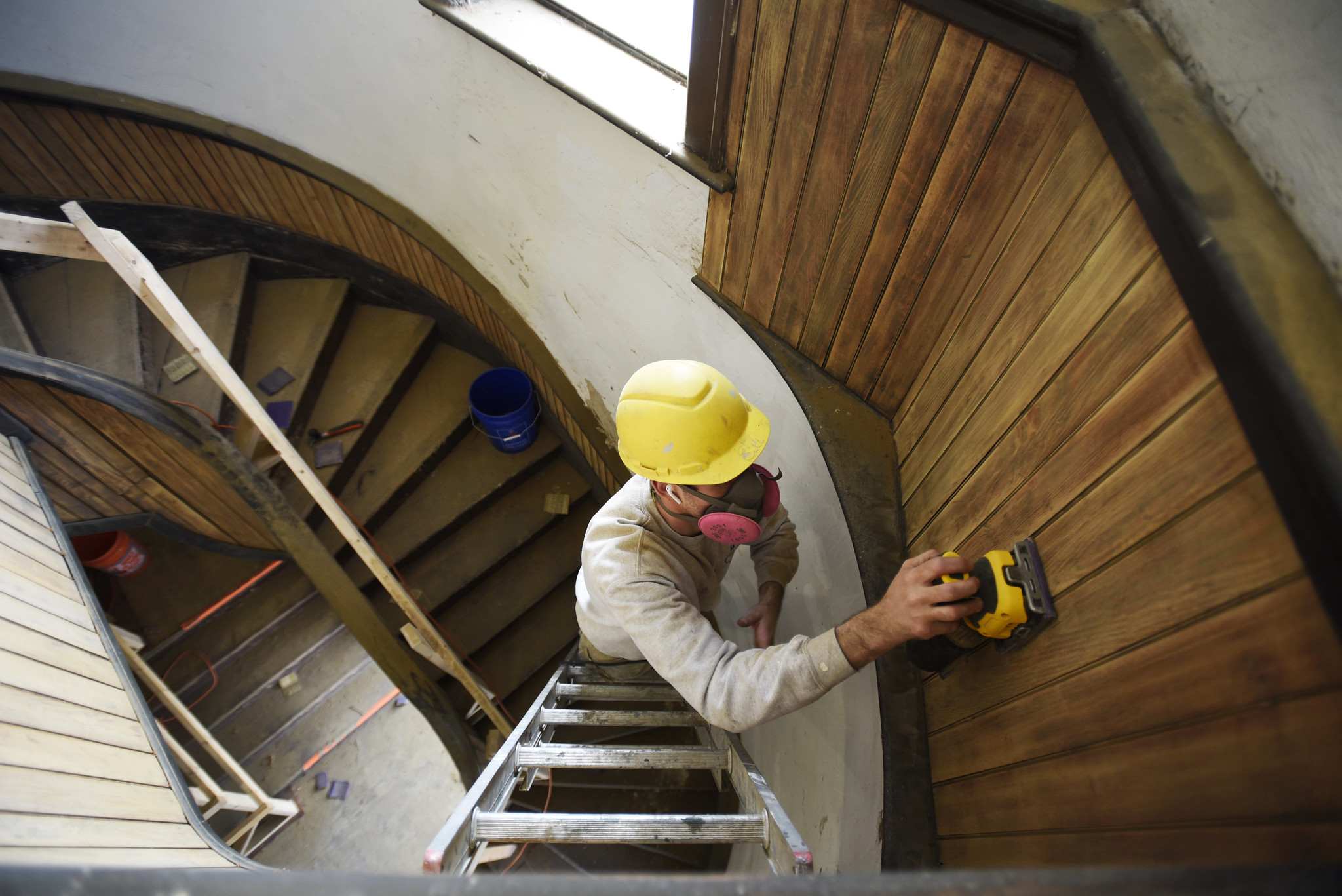 A construction worker refinishes original wood in a stairwell at Universal Preservation Hall in Saratoga Tuesday, April 9, 2019.