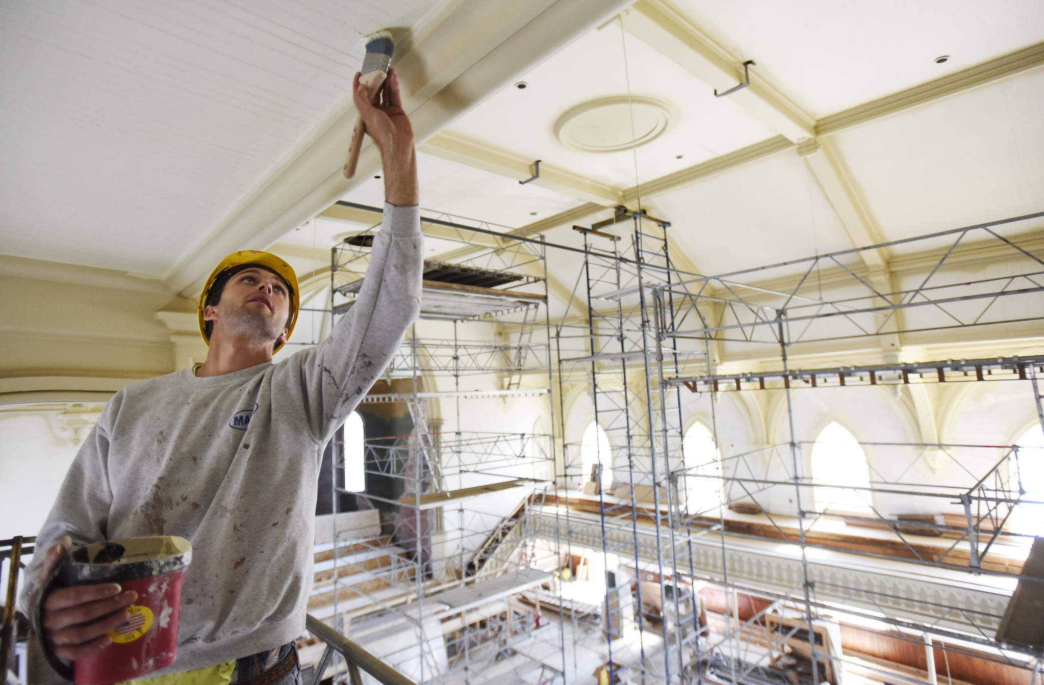 A construction worker touches up pain on the ceiling in the great hall at UPH in Saratoga Tuesday, June 4, 2019.