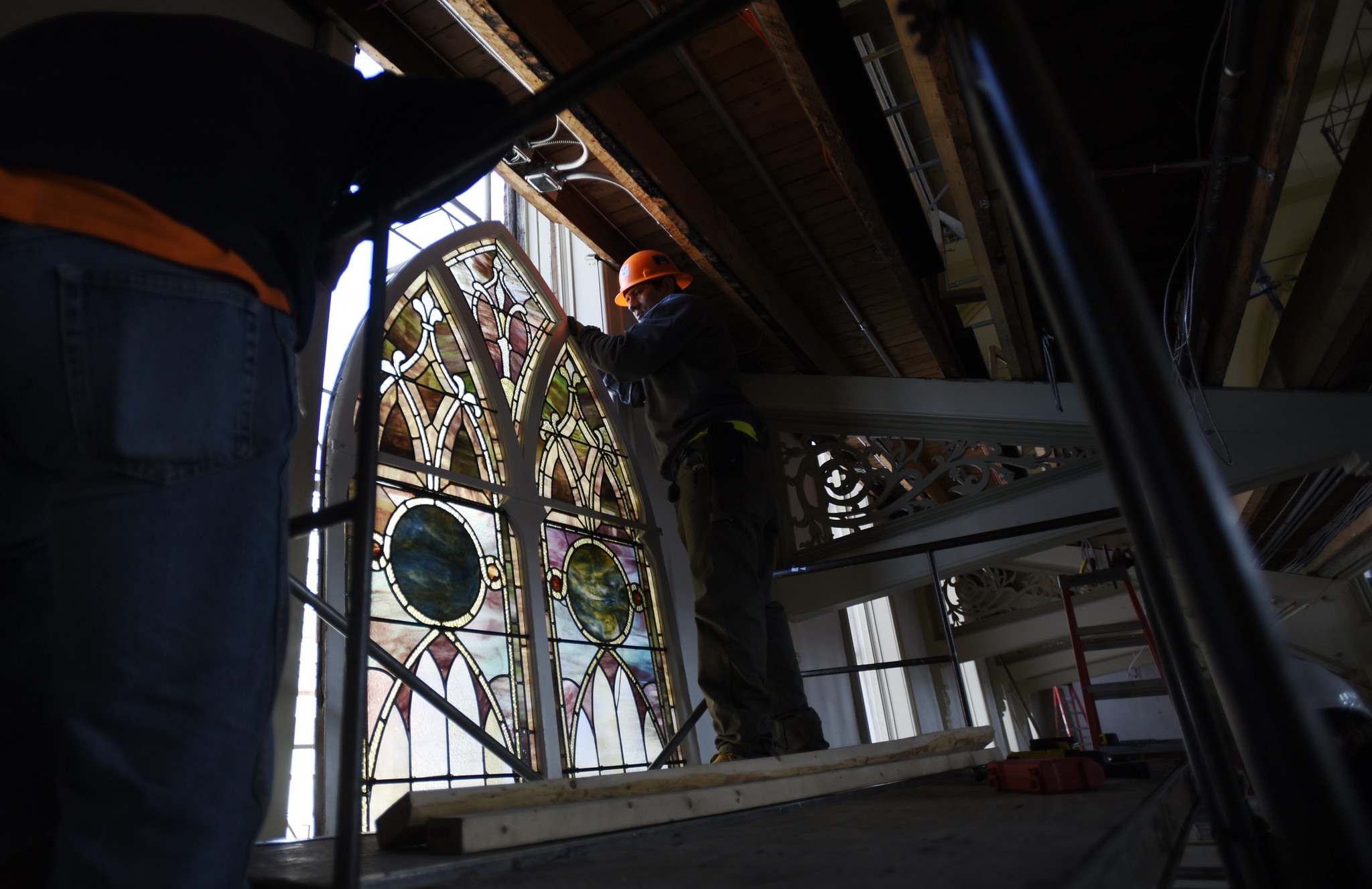 Crews install restored stained glass windows to their homes in the great hall at UPH in Saratoga Tuesday, June 4, 2019.